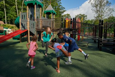 Lindsay Distefano, associate professor of kinesiology,shows children how to exercise on a playground at the Mansfield Community Center