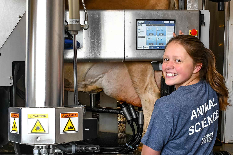 Female student utilizing robotic milking equipment