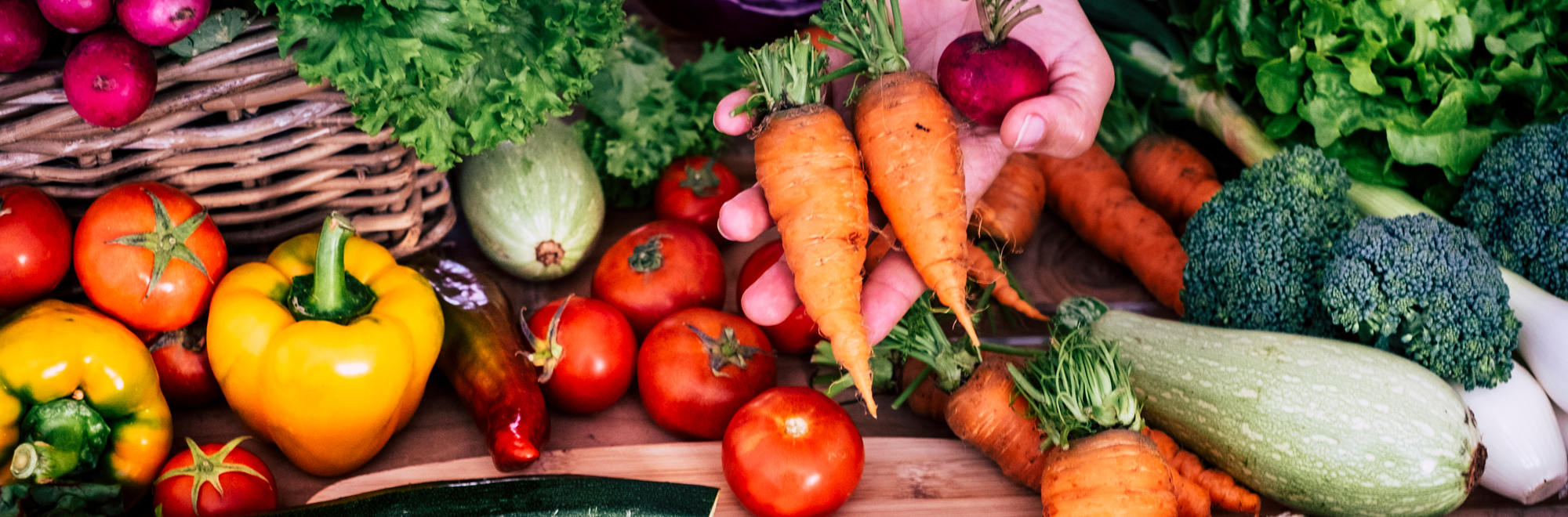 group of vegetables with a hand holding carrots