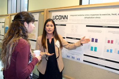 student presenting a poster at event