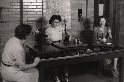 historical image of three women using scientific instruments