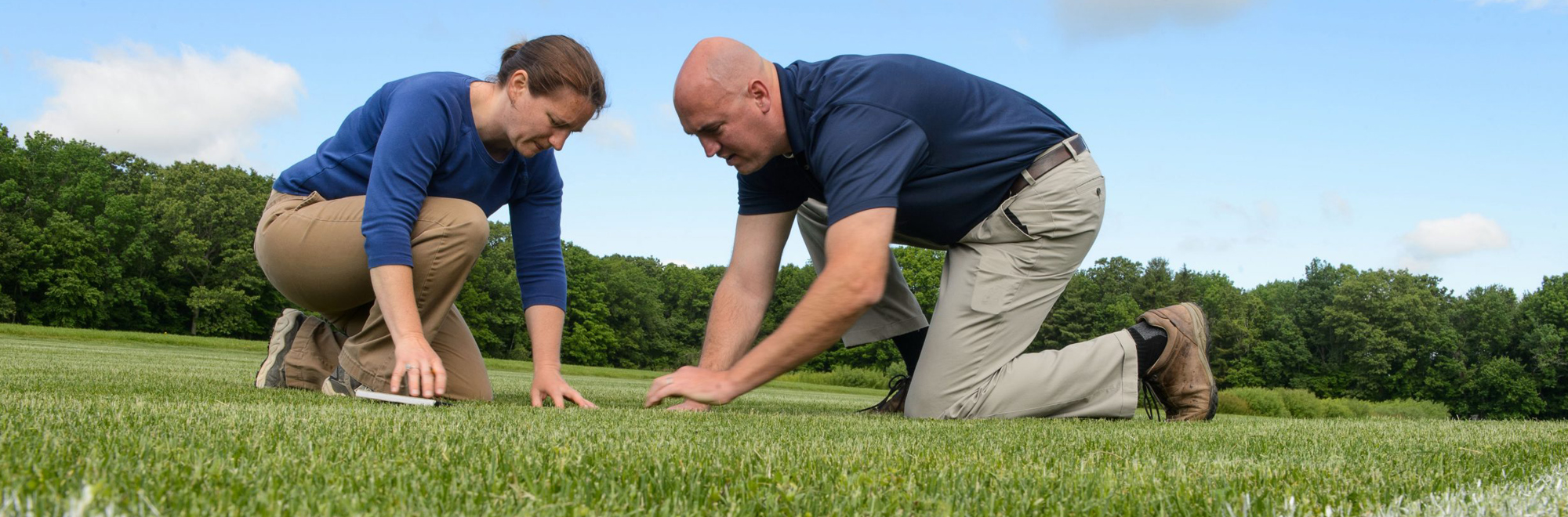 Julie Campbell and Jason Henderson are inspecting turfgrass