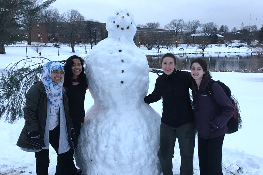 group posing with a snowman