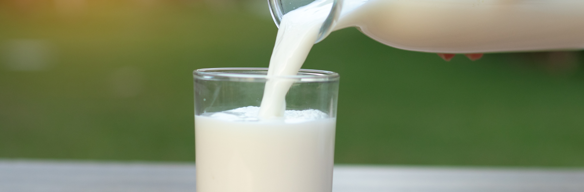 bottle of milk pouring into a glass
